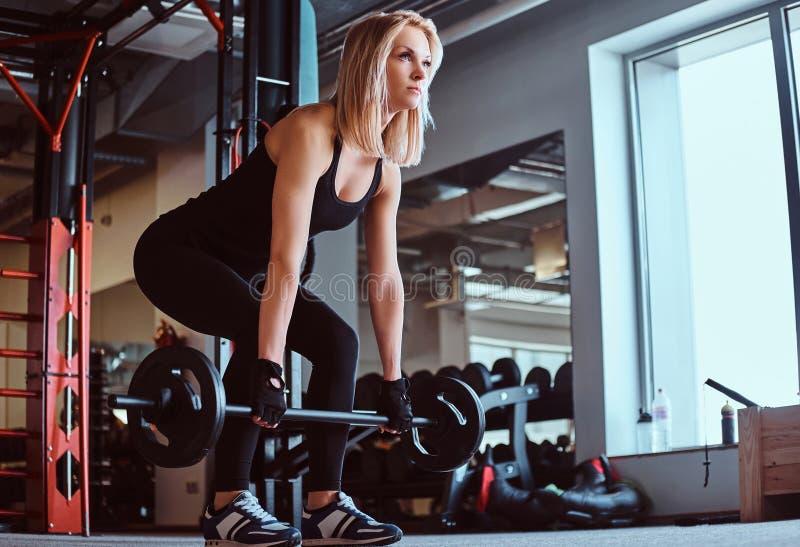 Femmina allegra bionda in abiti sportivi che fanno deadlift con il bilanciere nel club o nella palestra di forma fisica immagine stock