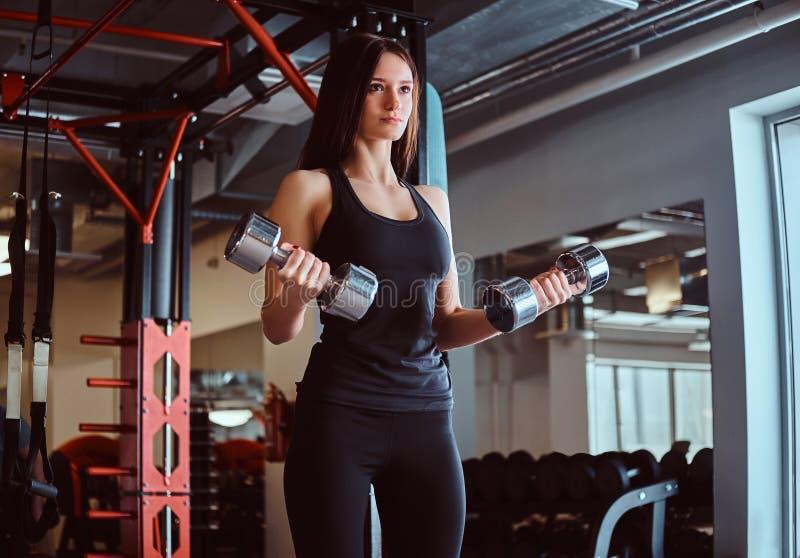 Femmina allegra bionda in abiti sportivi che fanno esercizio sul bicipite con le teste di legno in un club o in una palestra di f immagini stock libere da diritti