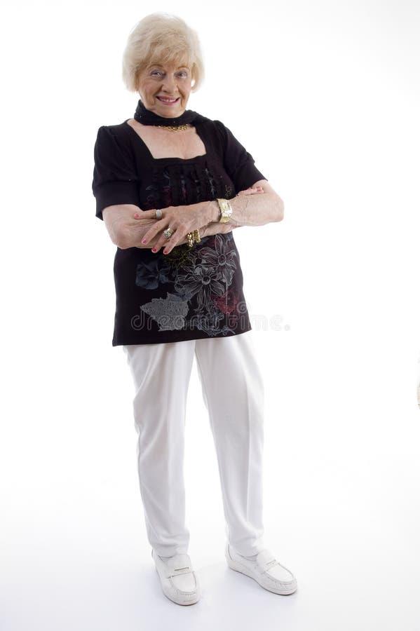 Femmina anziana diritta con le braccia attraversate fotografia stock