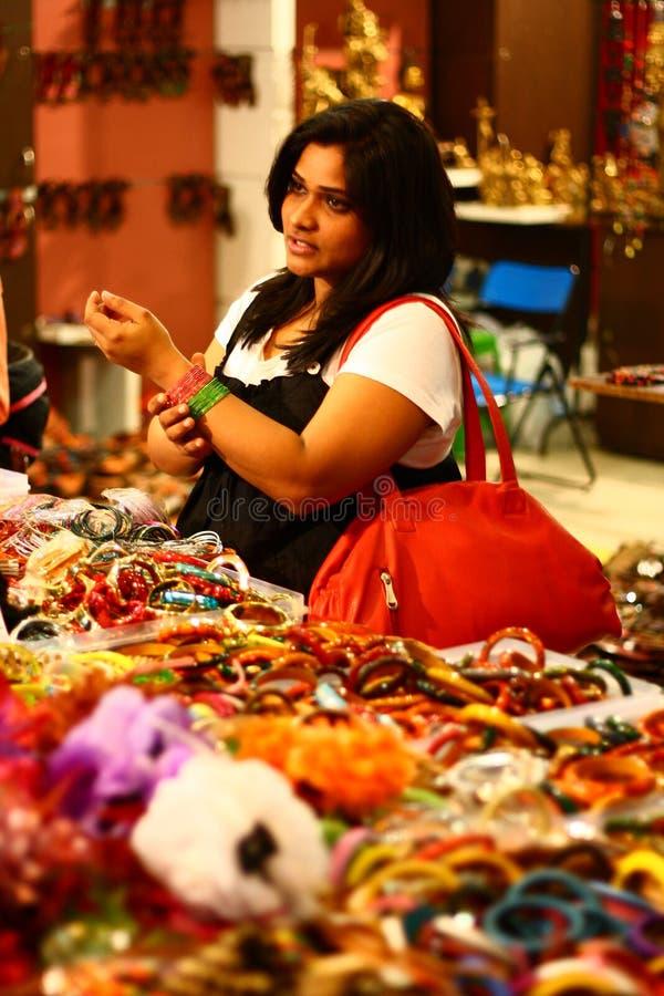Femmina asiatica che seleziona i braccialetti variopinti immagini stock libere da diritti