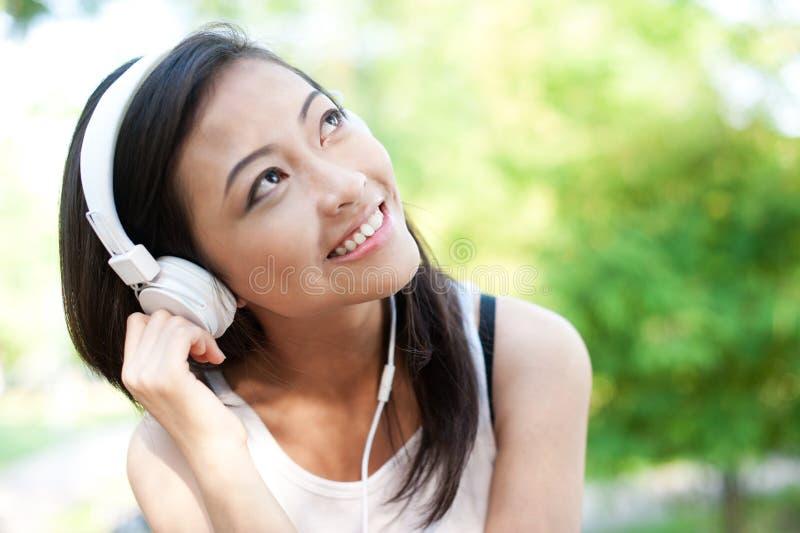 Femmina asiatica con le cuffie bianche immagini stock libere da diritti