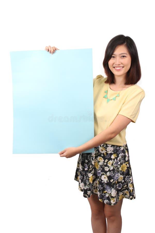 Femmina asiatica nell'abbigliamento casual che tiene avviso blu fotografia stock libera da diritti
