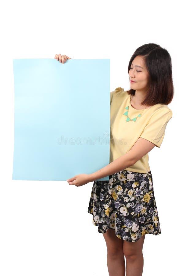 Femmina asiatica nell'abbigliamento casual che tiene avviso blu - serie 2 fotografia stock