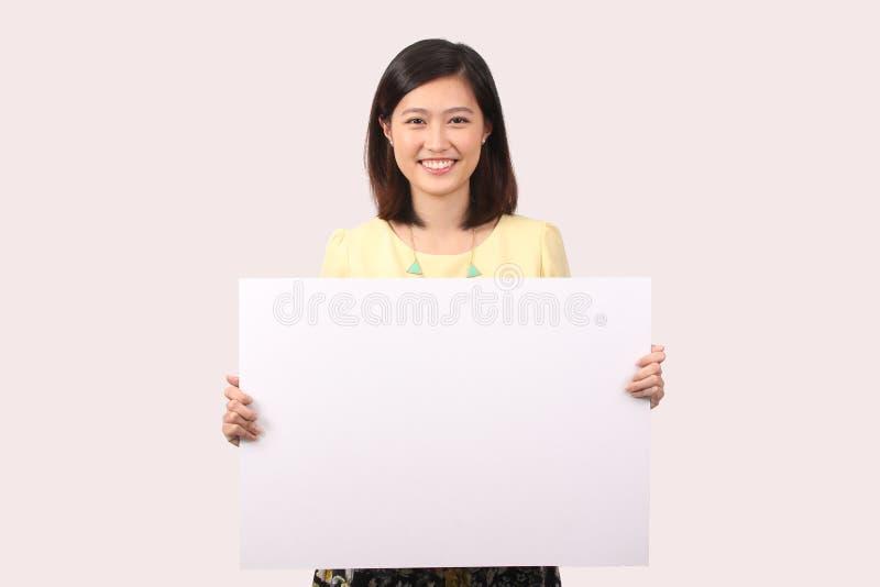 Femmina asiatica nella bacheca della tenuta di abbigliamento casual fotografia stock