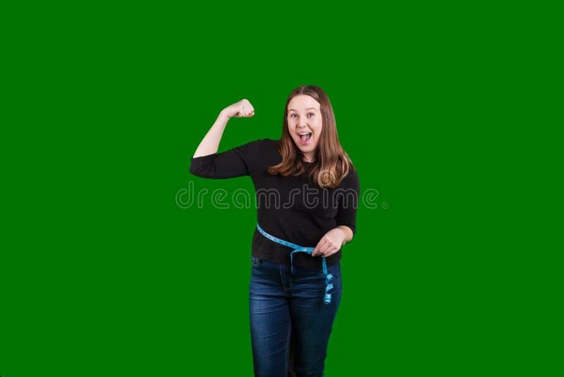 Femmina bionda che misura la sua vita che flette una riuscita espressione emozionante del braccio sul suo fronte fotografia stock