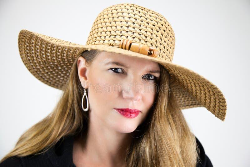 Femmina bionda matura del ritratto del primo piano in cappello e cappotto nero che esaminano macchina fotografica immagini stock libere da diritti
