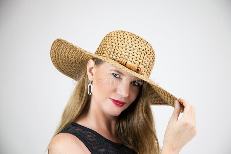 Femmina bionda matura del ritratto del primo piano con il cappello della tenuta che indossa cima nera che esamina macchina fotogr fotografia stock
