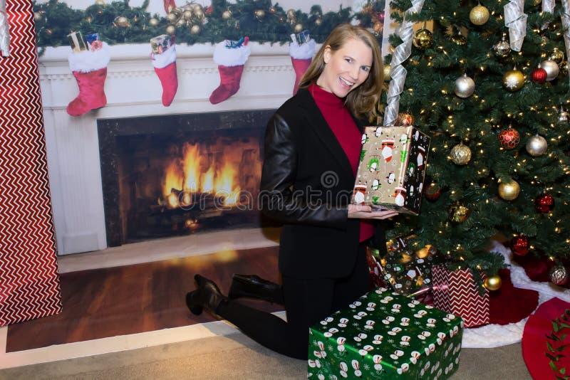 Femmina bionda in regali della tenuta di scena di festa accanto all'albero fotografia stock