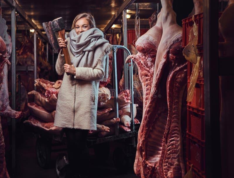 Femmina bionda in un rivestimento caldo in una conservazione in congelatore della carne fotografia stock