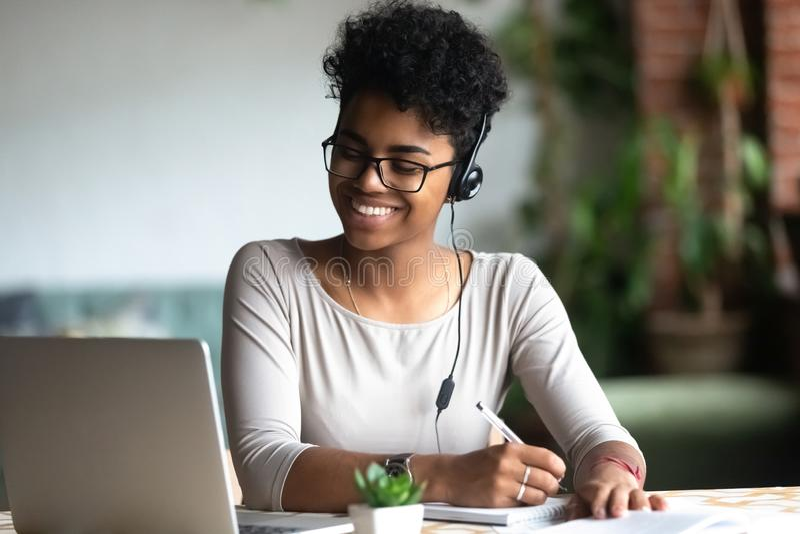 Femmina biraziale sorridente in cuffie che studia facendo le note fotografia stock libera da diritti