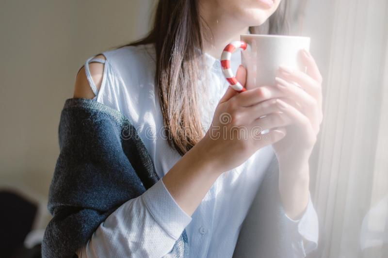 Femmina in camicia blu dalla finestra con la tazza del coffe immagine stock libera da diritti