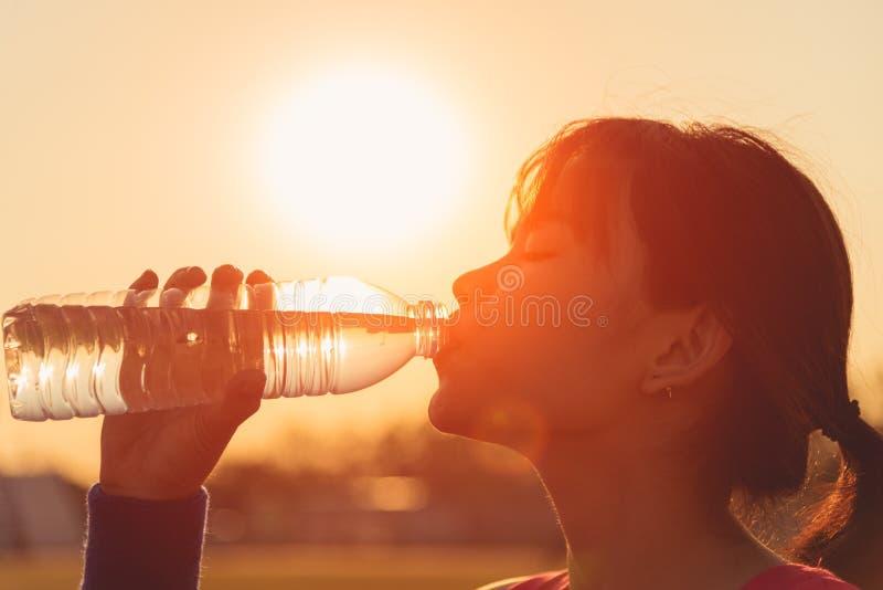 Femmina che beve una bottiglia di acqua fotografia stock