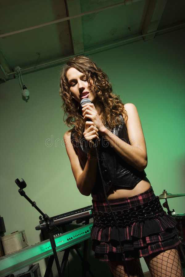 Femmina che canta nel mic. fotografia stock