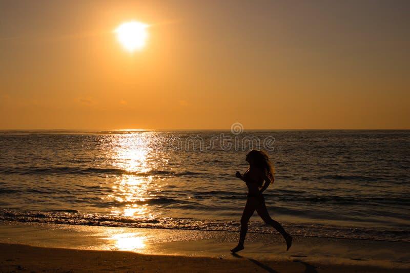 Femmina che funziona lungo la spiaggia fotografia stock