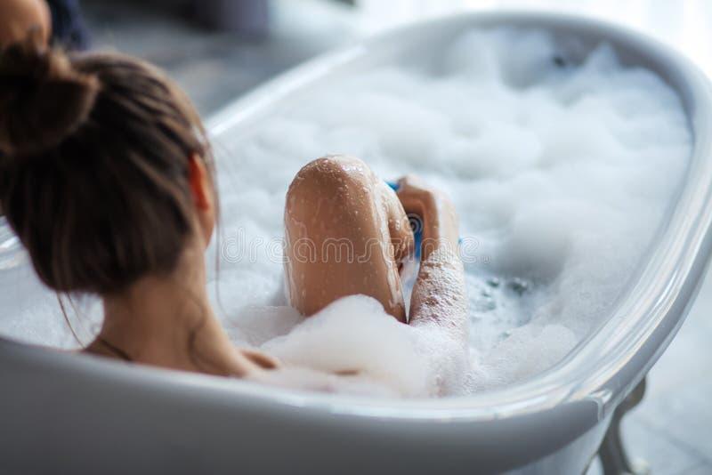Femmina che massaggia le sue gambe con la spugna nella vasca immagine stock libera da diritti