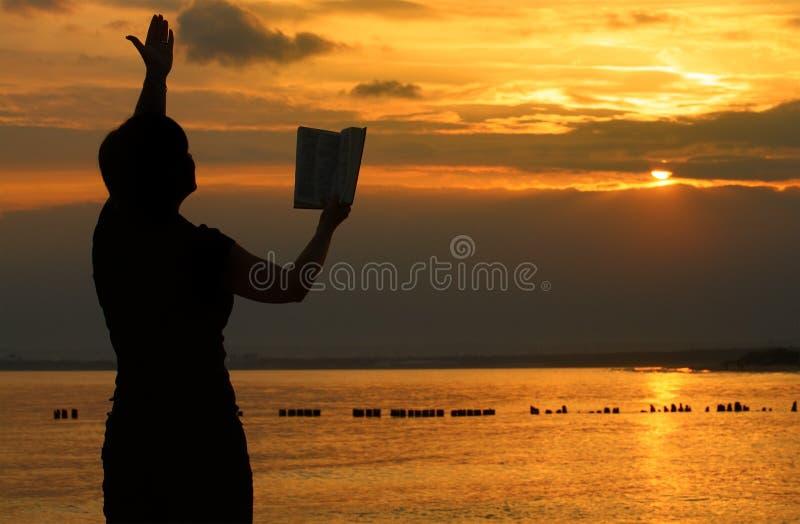 Femmina che prega con la bibbia immagine stock libera da diritti
