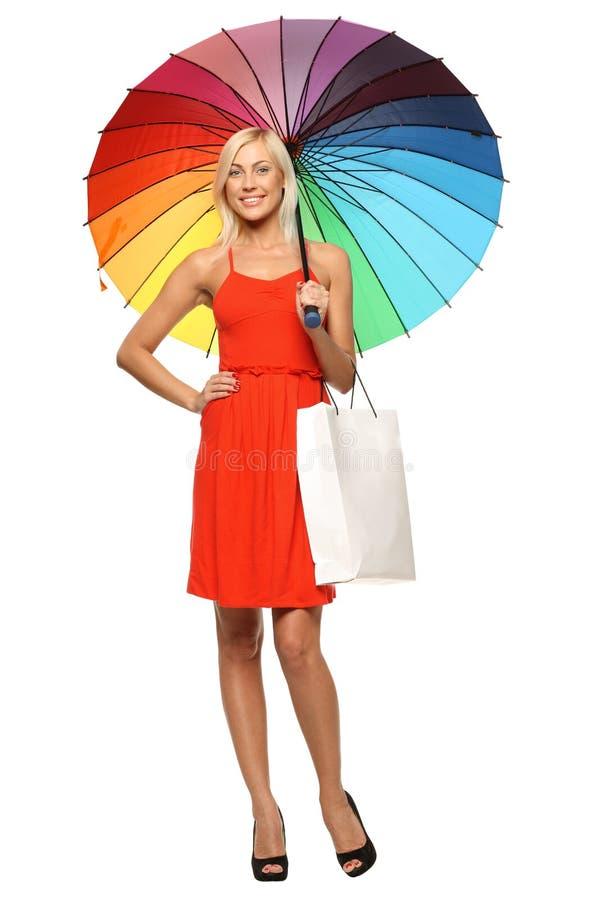 Femmina che si leva in piedi sotto l'ombrello con il sacchetto di acquisto fotografia stock