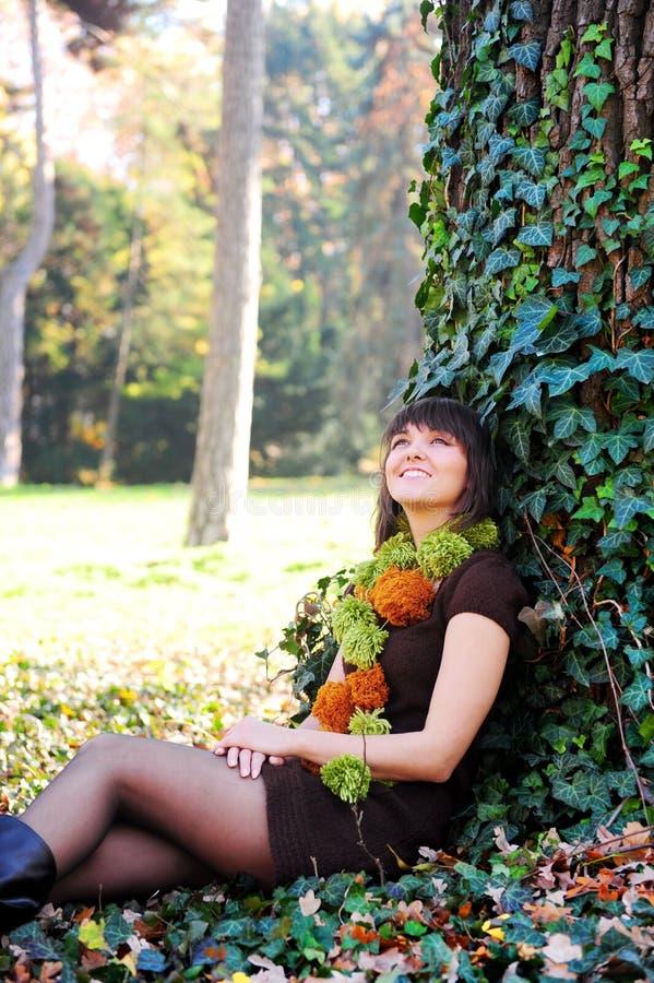 Femmina che si siede sotto un albero fotografia stock