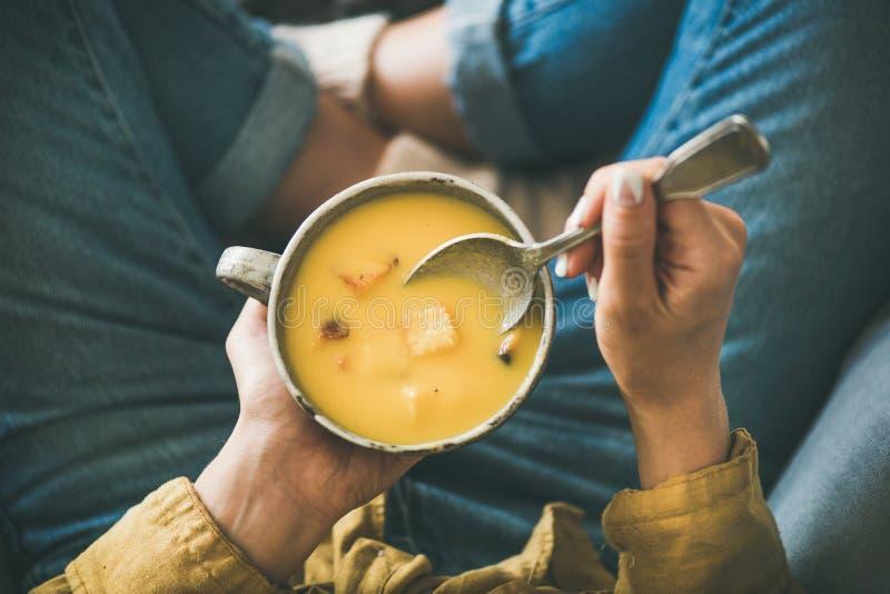 Femmina che si siede tenendo tazza della minestra crema di riscaldamento della zucca di caduta fotografia stock