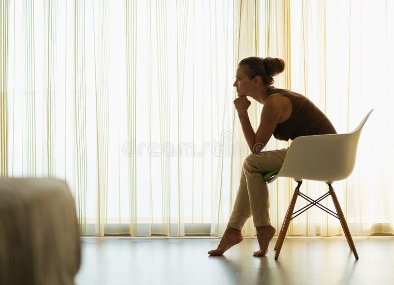 Femmina che si siede vicino alla finestra nella posa premurosa fotografia stock