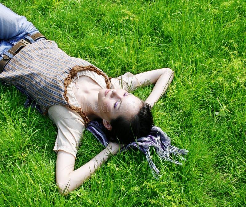 Femmina che si trova sull'erba fotografia stock