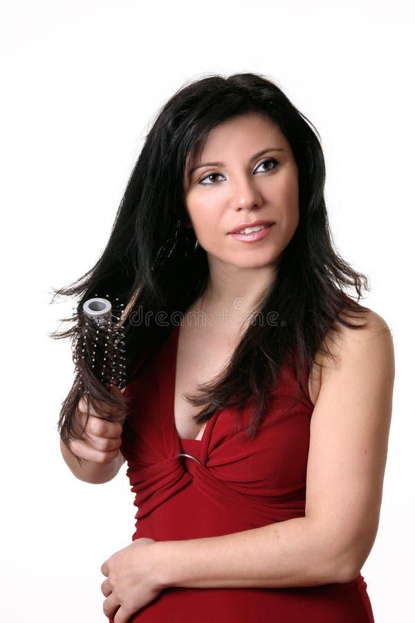 Femmina che spazzola i suoi capelli fotografie stock