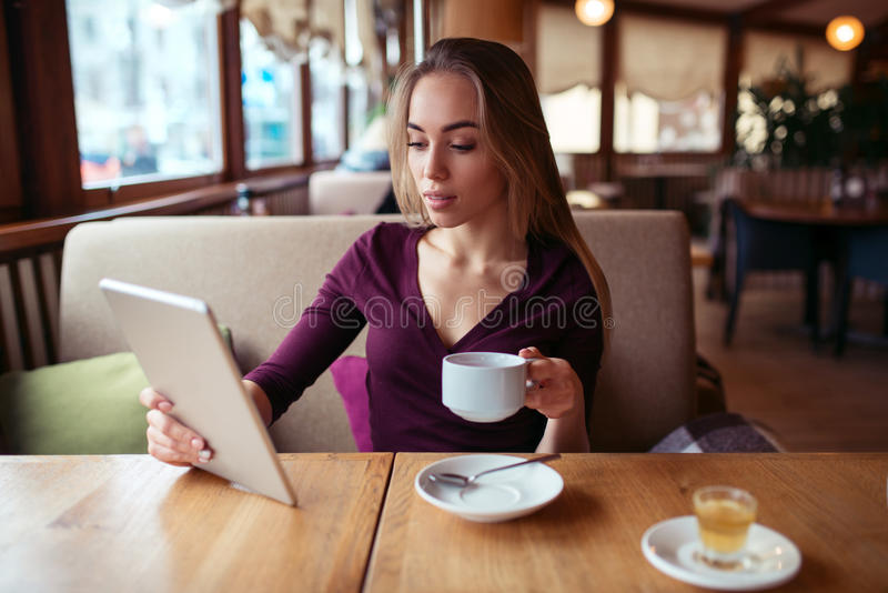 Femmina che utilizza wifi sul pc della compressa nel caffè fotografia stock libera da diritti