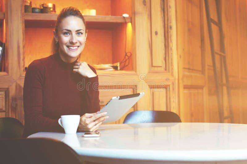 Femmina con il sorriso sveglio facendo uso della compressa digitale mentre rilassandosi durante il tempo di ricreazione fotografie stock libere da diritti