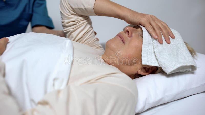 Femmina con la compressa su febbre di sofferenza della fronte, infermiere che si occupa del paziente immagini stock libere da diritti