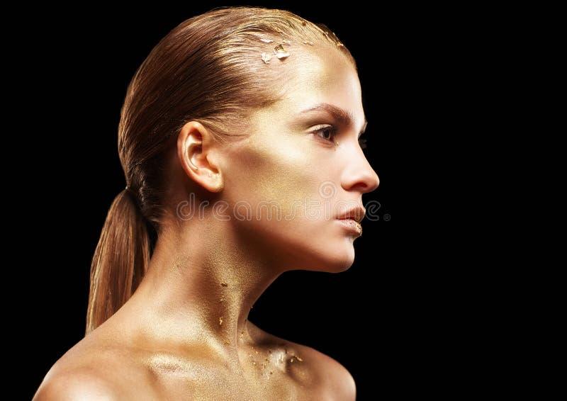 Femmina con trucco insolito del fronte del metallo Ragazza dorata sulla parte posteriore del nero fotografia stock libera da diritti