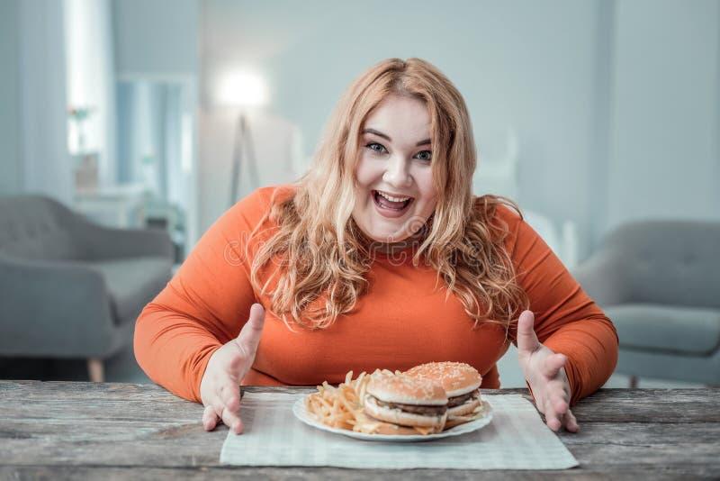 Femmina contentissima del positivo giovane che mangia alimenti a rapida preparazione fotografie stock libere da diritti