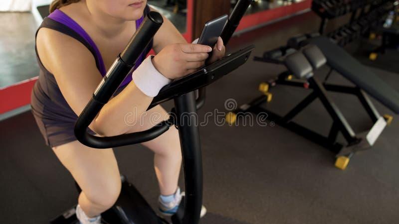 Femmina corpulenta pigra che pedaling lentamente bici fissa e che fa scorrere sul telefono immagine stock