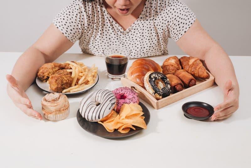 Femmina Curvy che prepara mangiare hamburger, problema di eccesso di cibo, depressione fotografie stock