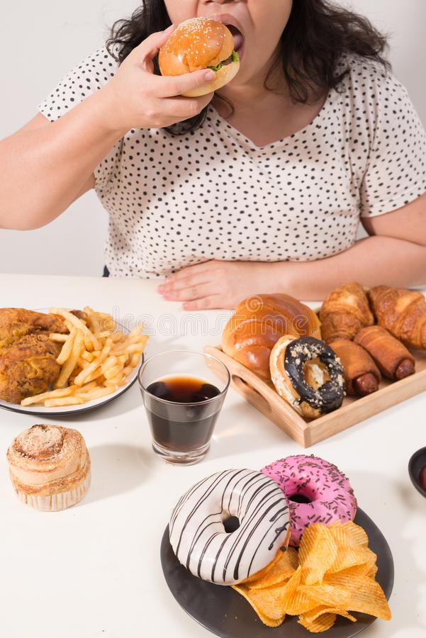 Femmina Curvy che prepara mangiare hamburger, problema di eccesso di cibo, depressione immagini stock