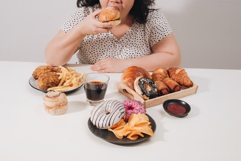 Femmina Curvy che prepara mangiare hamburger, problema di eccesso di cibo, reparto fotografie stock