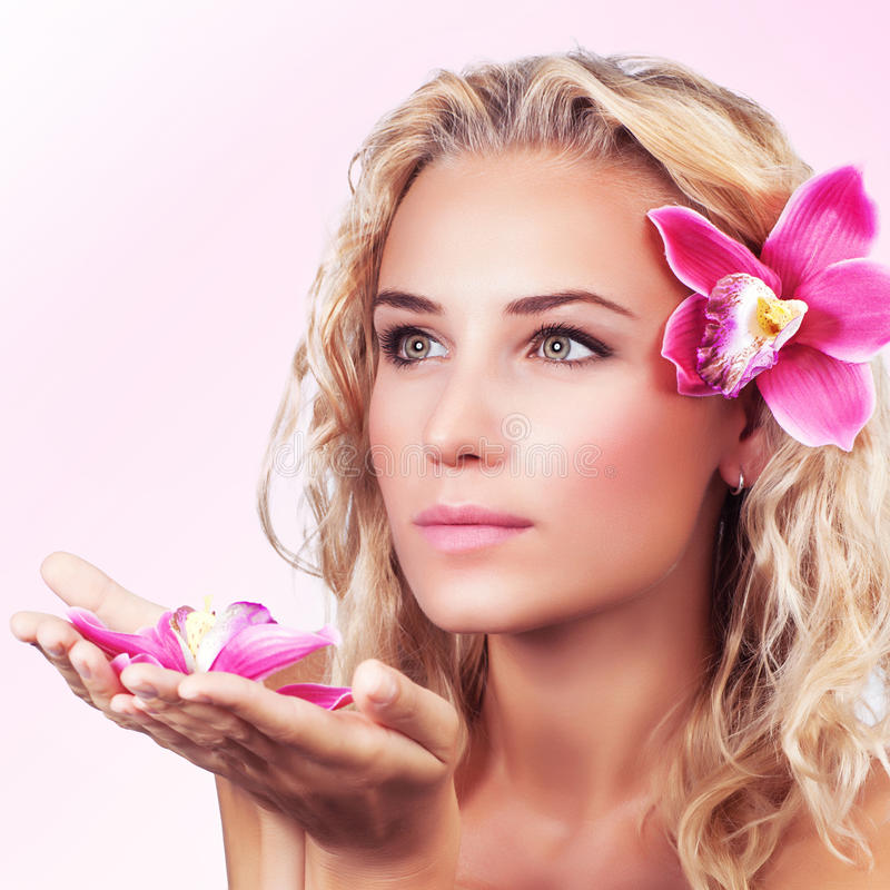 Femmina delicata con il fiore dell'orchidea fotografia stock