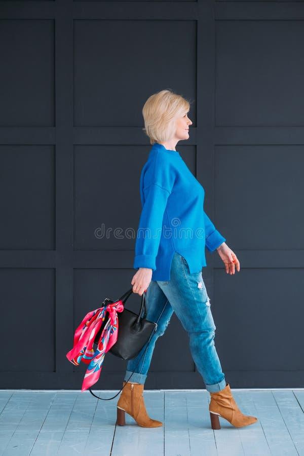 Femmina di fiducia della donna che cammina attrezzatura blu casuale immagini stock libere da diritti