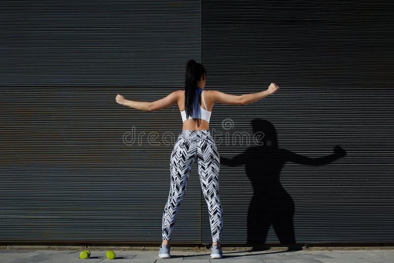 Femmina di misura in abiti sportivi che si esercita sul fondo nero all'aperto fotografie stock libere da diritti