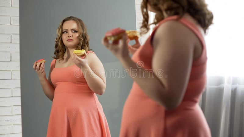 Femmina di peso eccessivo depressa che mangia le guarnizioni di gomma piuma davanti allo specchio, disordine alimentare immagini stock
