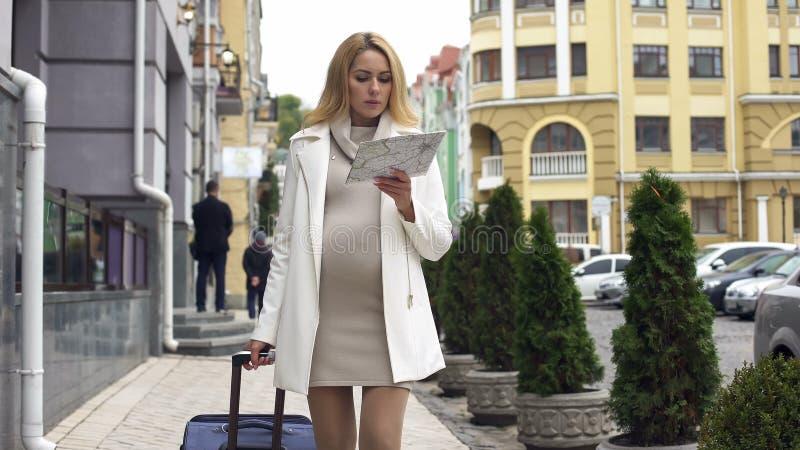 Femmina di previsione attraente con la valigia che cerca clinica in città, viaggio fotografia stock