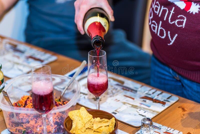 Femmina incinta in bottiglia della tenuta del pullover di natale e vino non alcolico di versamento di rosso nel vetro del champag fotografia stock libera da diritti
