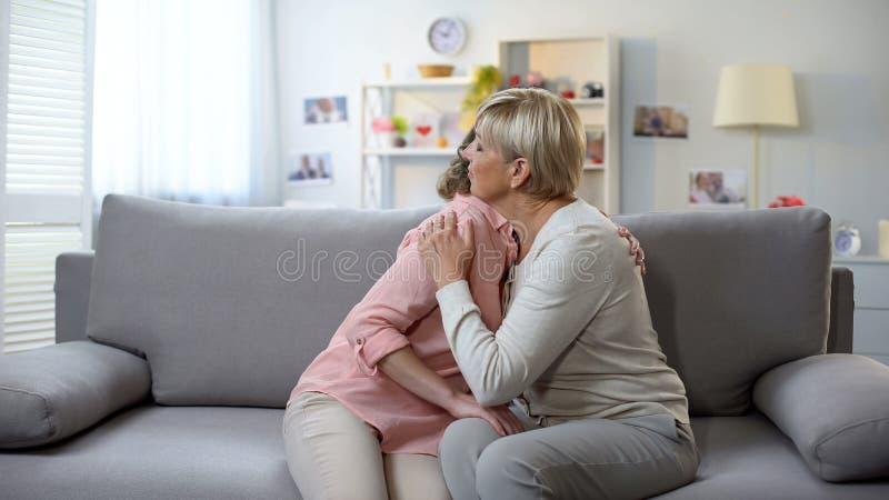 Femmina infelice e figlia mature che abbracciano sul sofà, sul disfacimento di perdita e sul supporto immagine stock