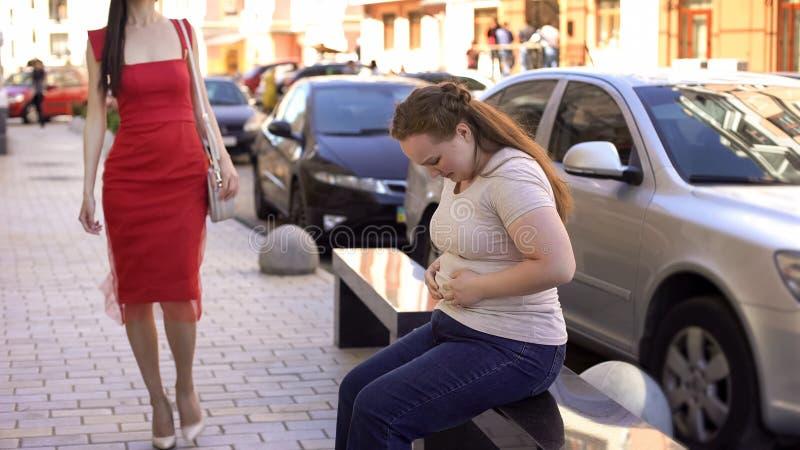 Femmina obesa che esamina disperatamente la pancia grassa, bella signora esile che passa vicino fotografie stock