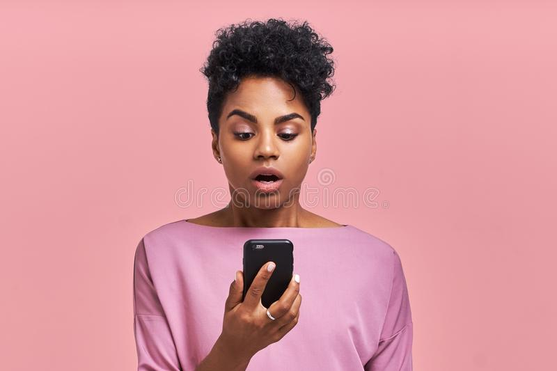 Femmina pelata scura riccia attraente con i sembrare dell'acconciatura di afro agitati allo schermo dello smartphone, impressiona immagini stock libere da diritti