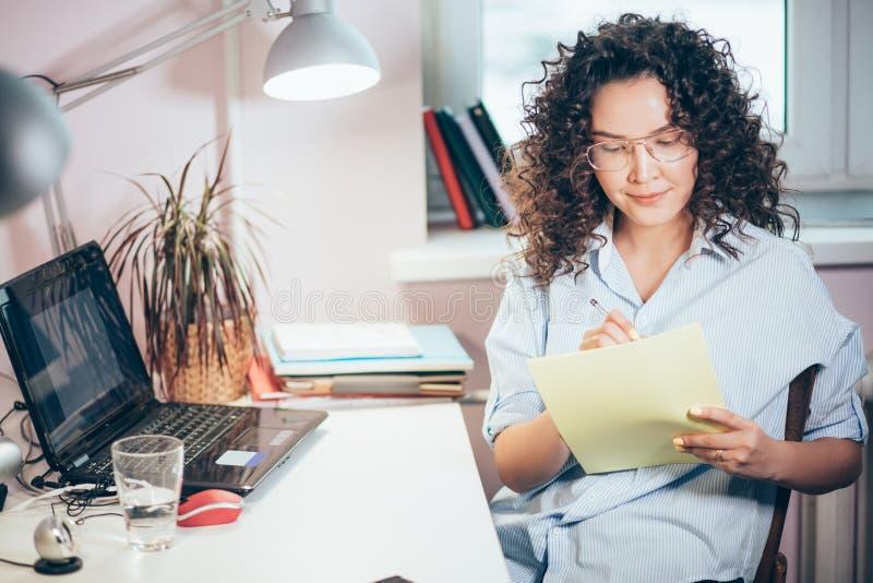 Femmina piacevole con capelli ondulati che fanno compito Scrivendo sul documento fotografia stock libera da diritti