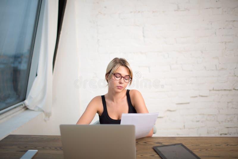 Femmina in in riassunto esperto della lettura del responsabile di vetro, seduta nell'interno dell'ufficio immagine stock libera da diritti