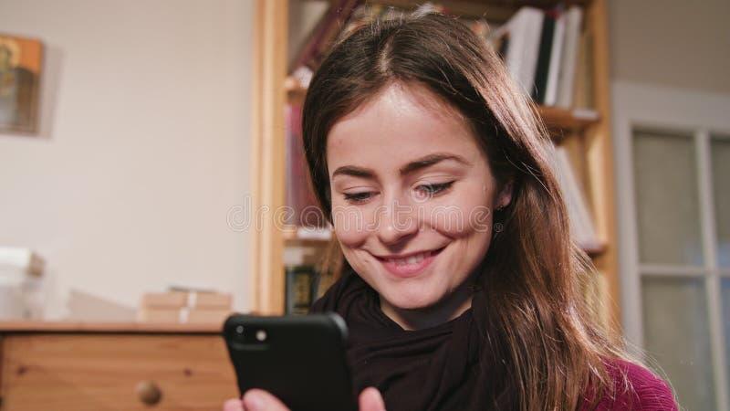 Femmina sorridente che per mezzo del telefono fotografie stock