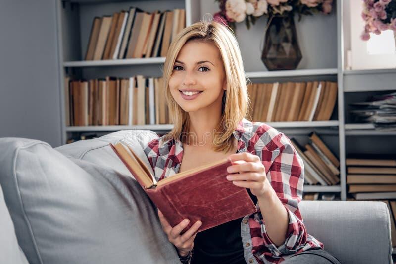Femmina sorridente che tiene un libro fotografia stock