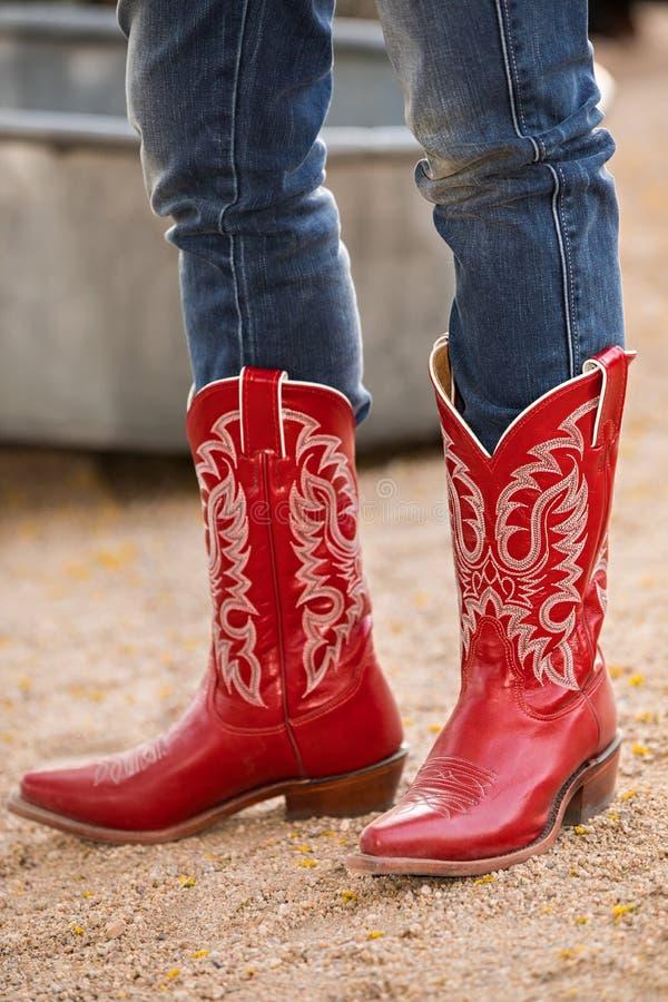 Femmina in stivali di cowboy rossi sulla strada della ghiaia immagini stock libere da diritti