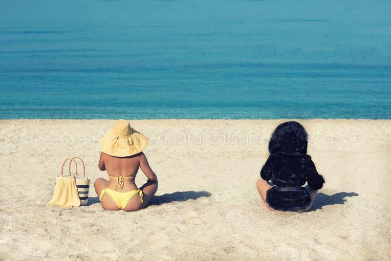 Femmina in un costume da bagno e un cappello giallo e una ragazza in una pelliccia sulla spiaggia Immagine concettuale dell'inver immagine stock